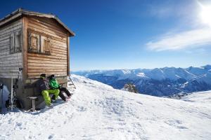 Skifahrer sitzen bei einer Hütte am Berg in Graubünden, Schweiz ALDI SUISSE TOURS