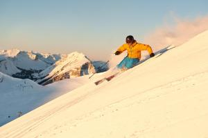 © Alex Kaiser - Bergbahnen Diedamskopf | Skifahren auf der Skipiste bei Sonnenaufgang am Diedamskopf in Schoppernau, Vorarlberg ALDI SUISSE TOURS